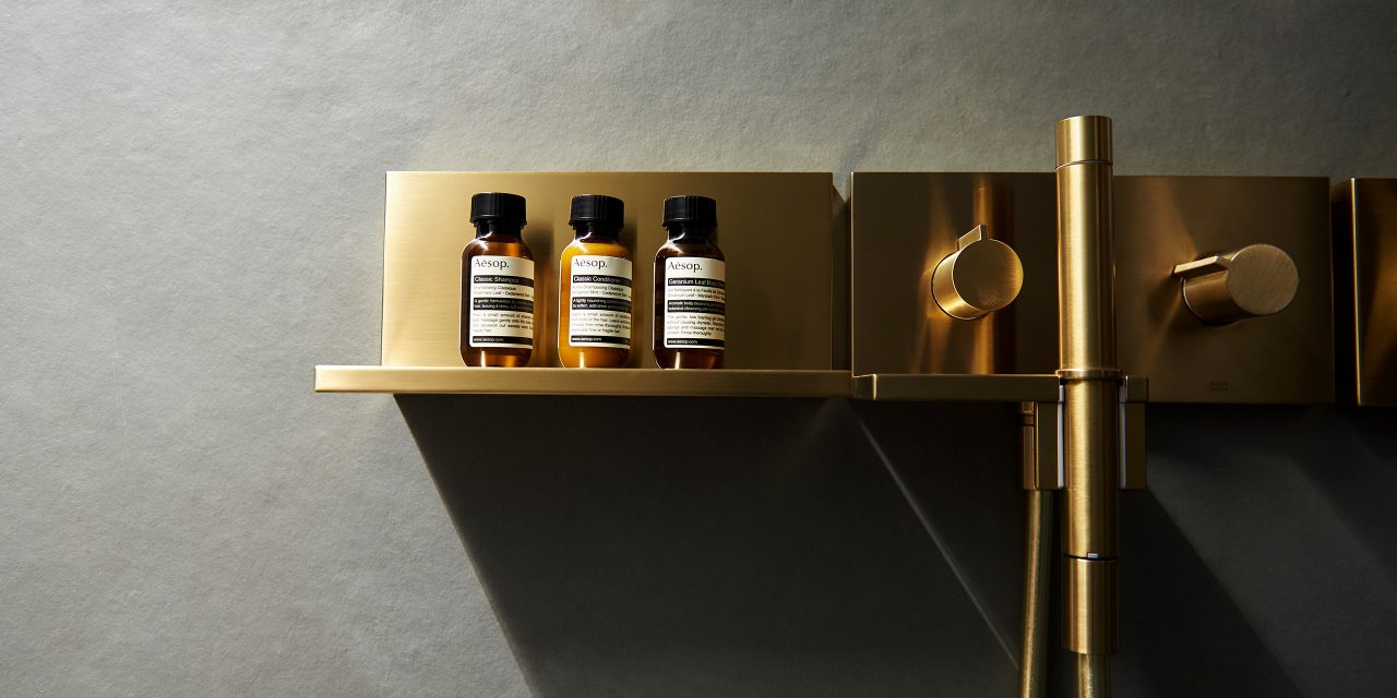A golden shelf with three small bottles next to the shower armature