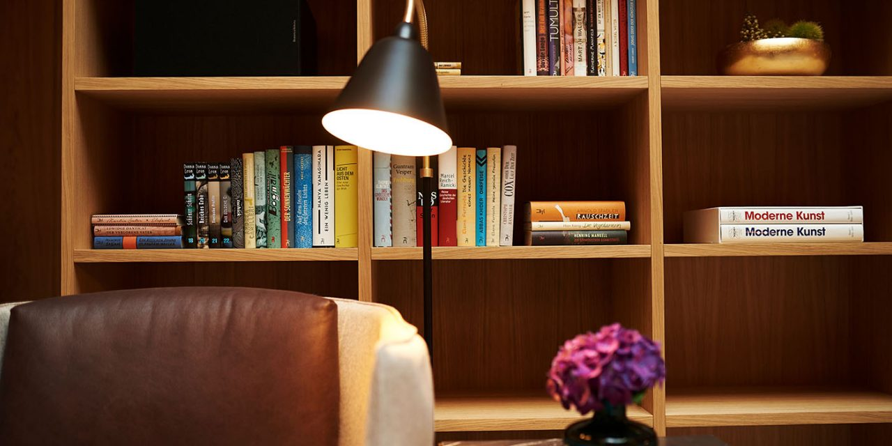 An armchair stands in front of a large wooden shelf in which many books can be found in the BEYOND Hotel in downtown Munich.