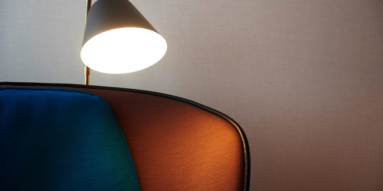 Black-golden standard lamp stands behind an armchair in the BEYOND hotel in downtown Munich