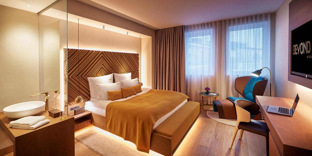 A category B room in the BEYOND-Hotel Munich with a wooden washbasin with golden fittings, armchair, desk and comfortable bed.