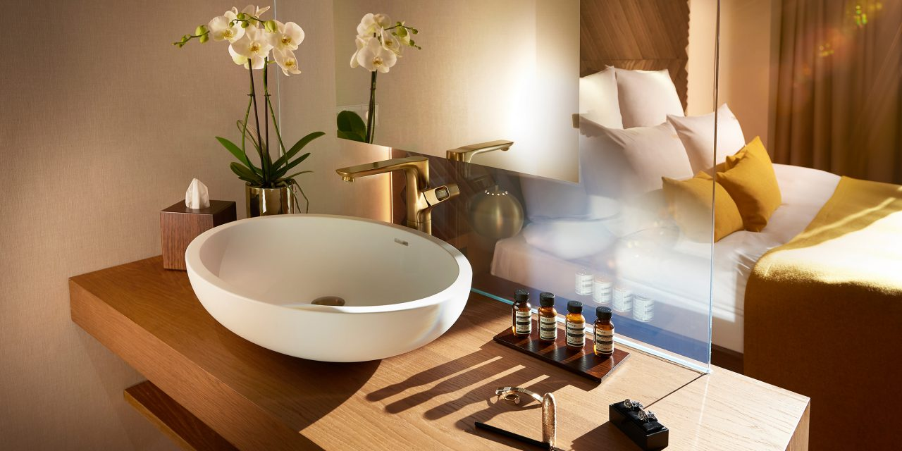 View from an open bathroom with washbasin and several cosmetics into a light-flooded hotel room in BEYOND-Munich.