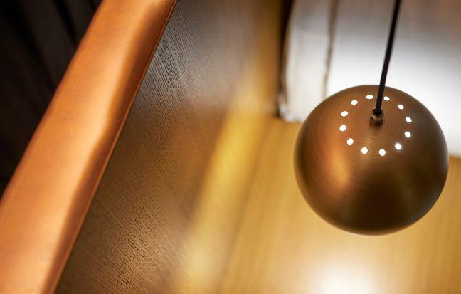Lampe am Bett im Schlafzimmer in Kupfertönen
