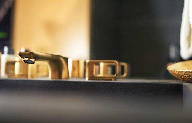 goldene Armatur des schwarzen Waschbeckens mit verschiedenen Pflegeprodukten und Goldschale