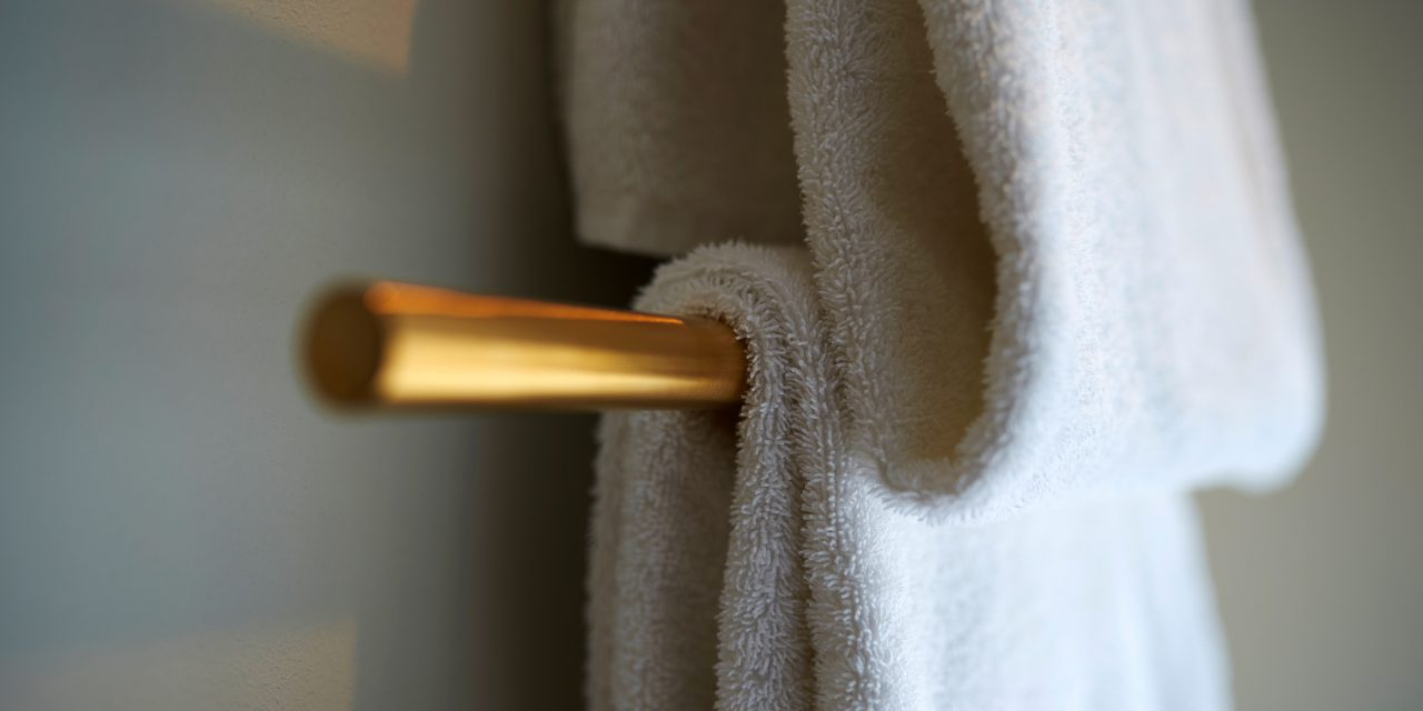 A towel lies over a golden towel holder