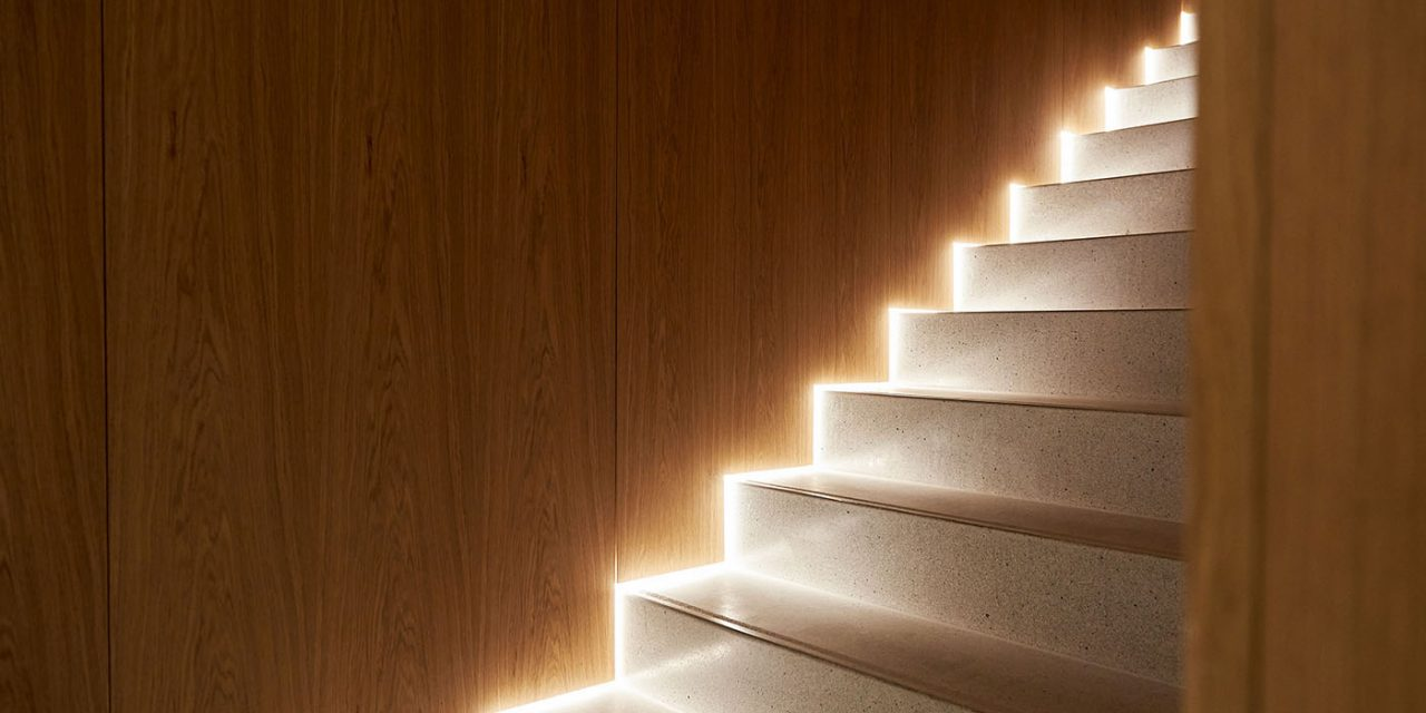 Close-up of a staircase with wood-panelled walls and indirectly illuminated steps.