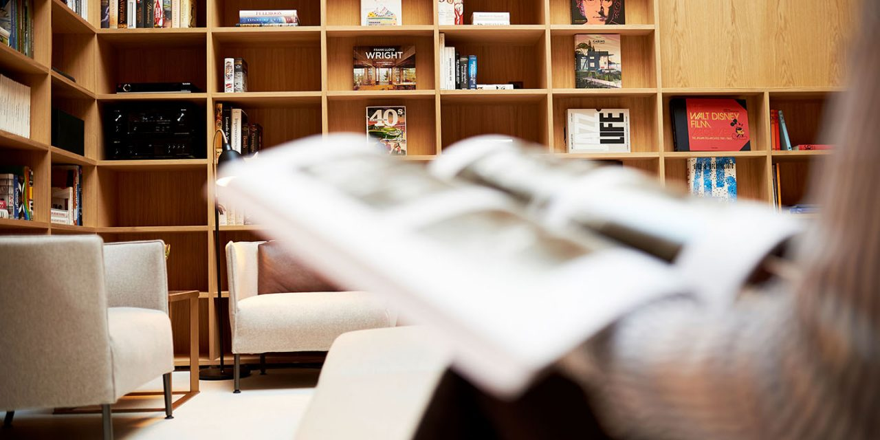 A large wooden bookshelf in the BEYOND-Hotel Munich - in the foreground a reading guest can be seen.