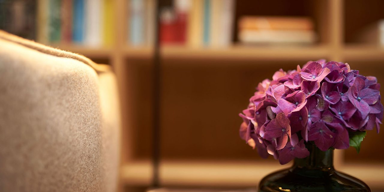 Close-up of a bouquet of flowers, in the background a wooden shelf with several books is blurred.