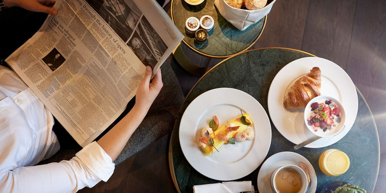 Ein Gast liest die aktuelle Zeitung, neben ihm stehen auf einem kleinen Tischchen mehrere Teller mit Frühstück.