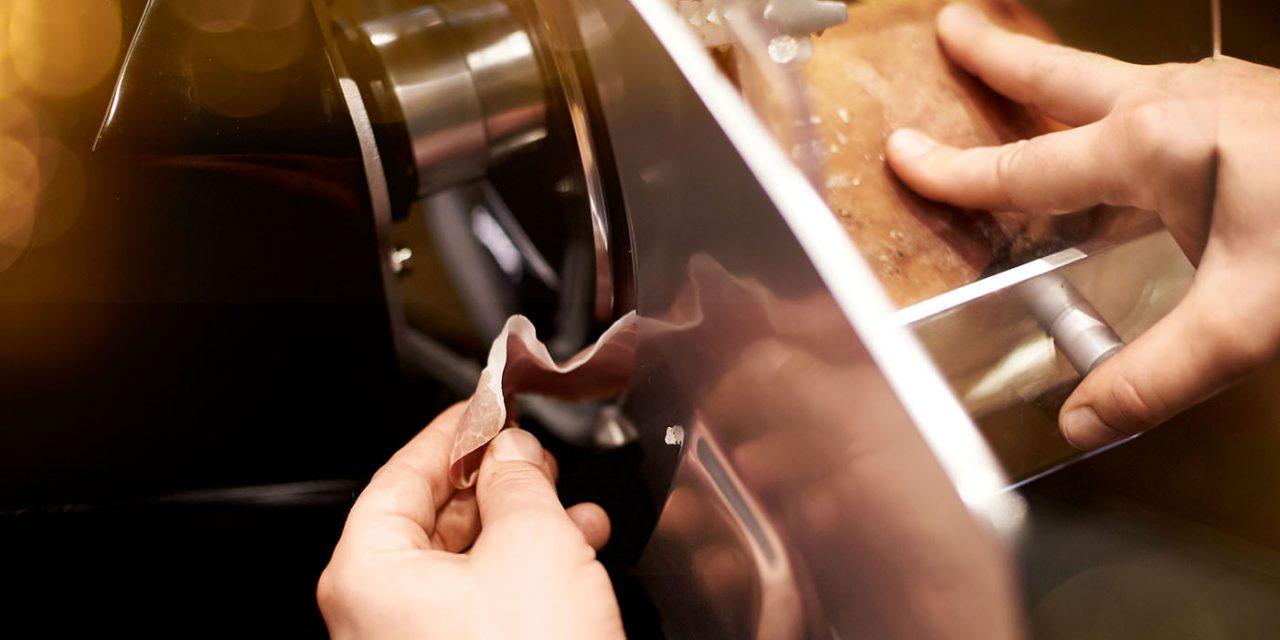 Ein Koch im BEYOND-Hotel schneidet mit einer Schneidemaschine dünne Speckscheiben.