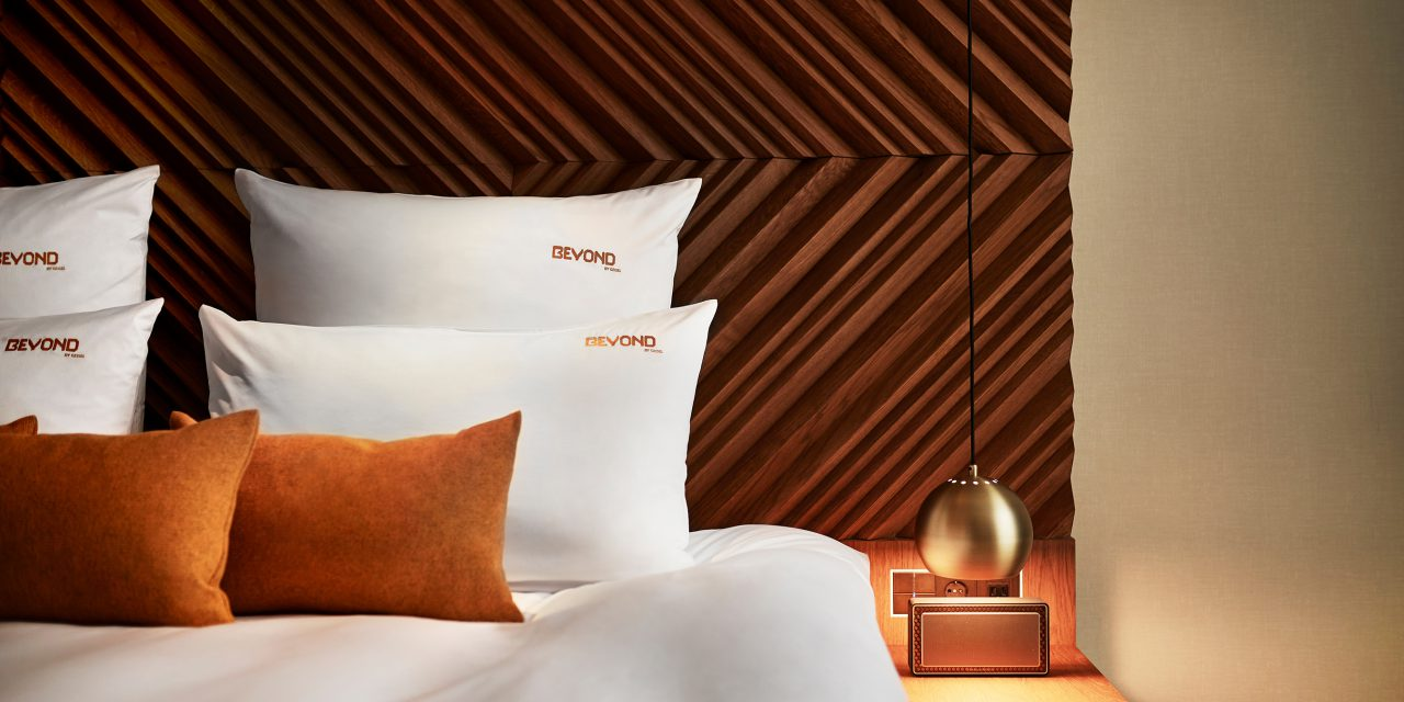 Close-up of a hotel bed in the BEYOND-Hotel Munich with several embroidered cushions and a Bluetooth box on the bedside table.