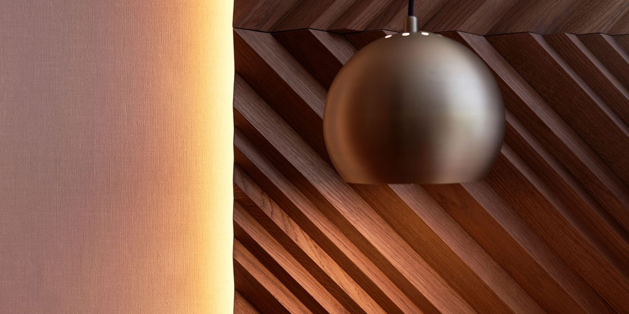 A golden hanging lamp hangs in front of the wooden bed headboard in the BEYOND-Hotel Munich.
