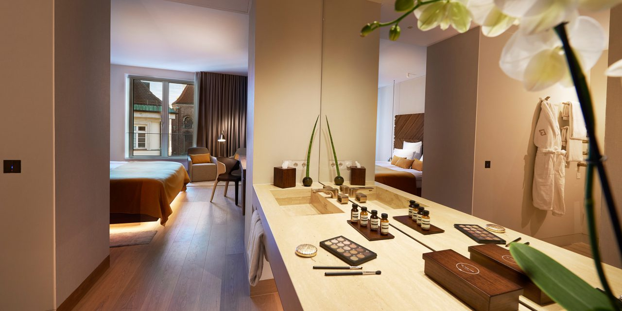 View through an open bathroom, with a washbasin and various cosmetic products on the right, into a spacious hotel room in the BEYOND-Hotel.
