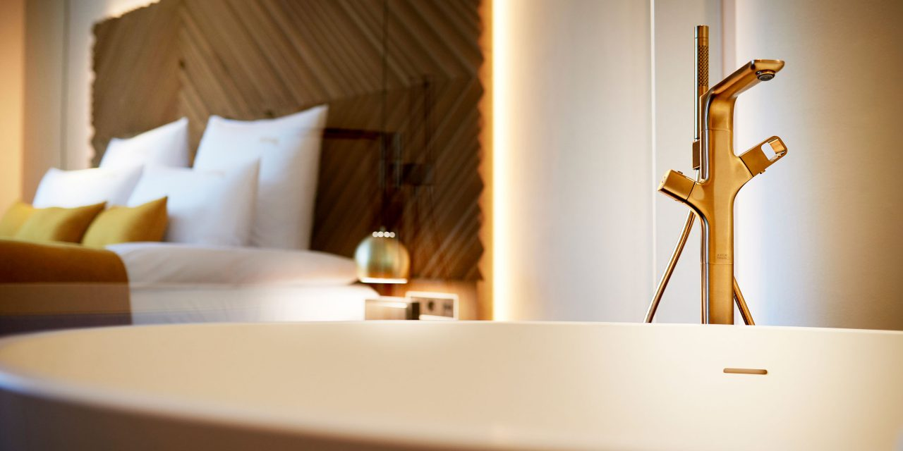 A free-standing bathtub with a golden fitting in the BEYOND-Hotel Munich - in the background you can see the hotel bed.