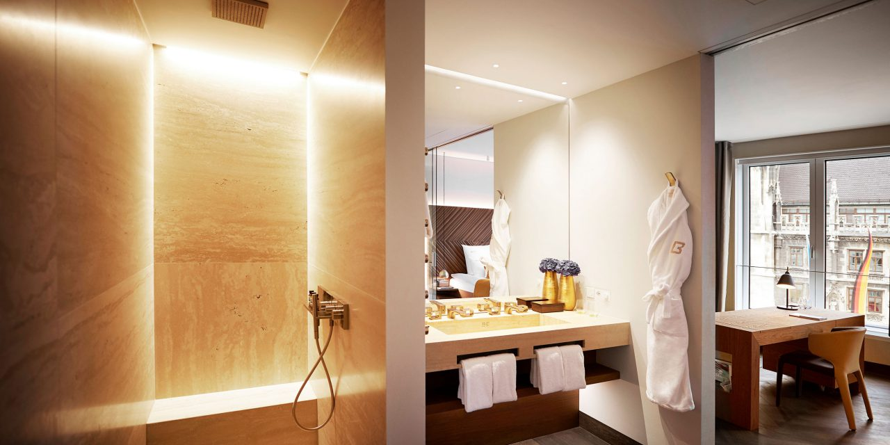 A spacious bathroom with a rain shower on the left and a washbasin with mirror on the right - a bathrobe with the BEYOND logo hangs on the wall.