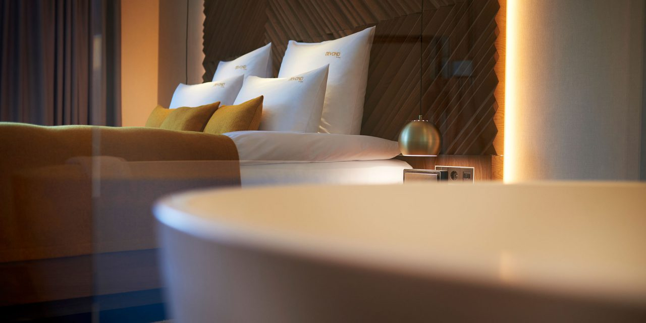 View into a room with a comfortable bed, in the foreground a bathtub in the BEYOND-Hotel Munich is blurred.