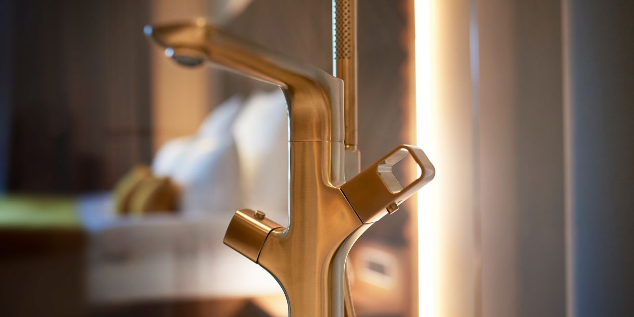 The golden armature of a bath tub, in the background the hotel bed is blurred to recognize.