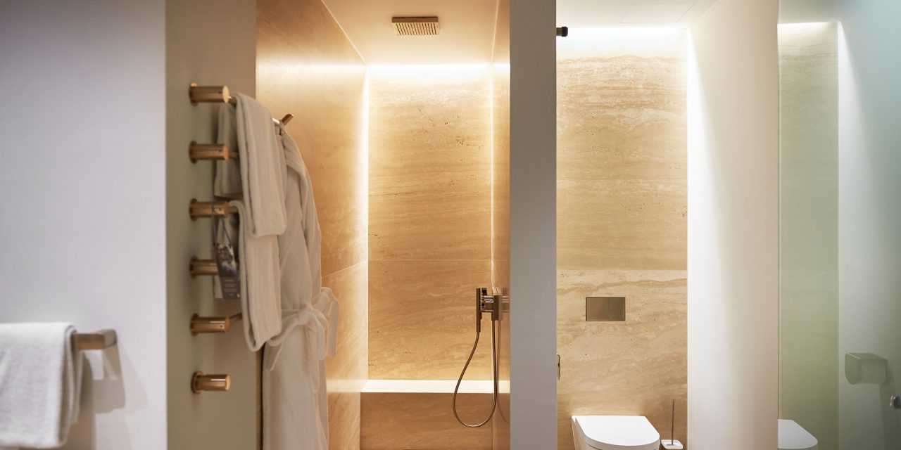 View into a bathroom of the BEYOND-Hotel Munich with rain shower and indirect lighting