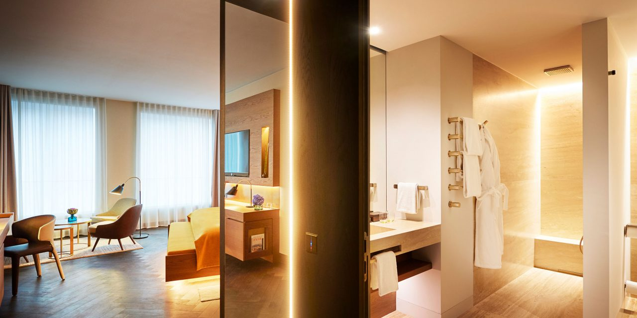 A spacious and bright hotel room with a seating group and floor-to-ceiling windows, next to it a bathroom with rain shower.