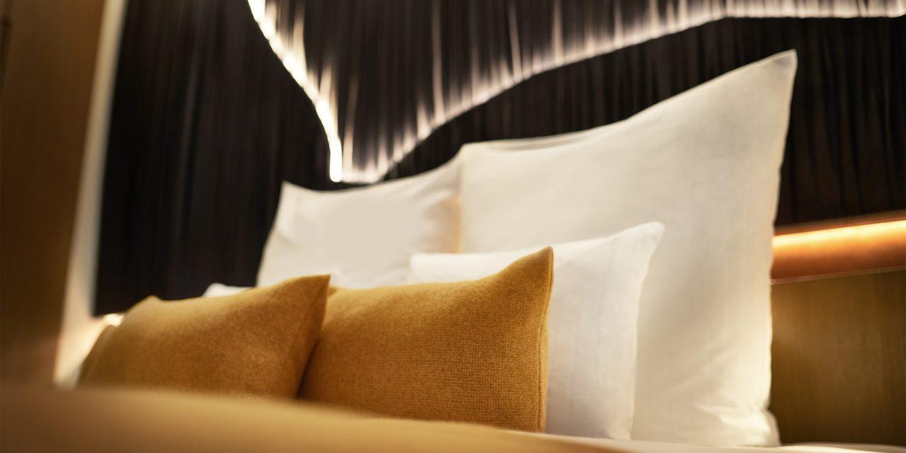 Schön hergerichtetes Bett mit mehreren Kissen im BEYOND-Hotel München