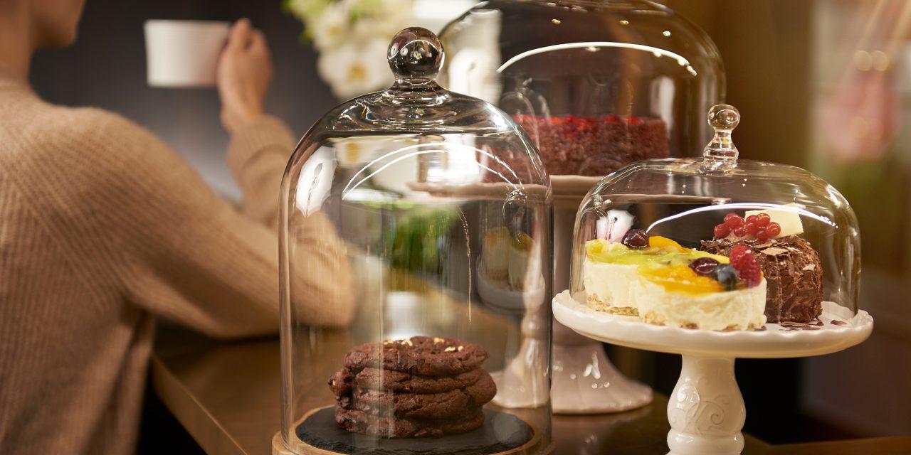 Drei Kuchenständer mit verschiedenen Kuchen und Keksen stehen auf einem Tresen im Hotel in der Münchener Innenstadt