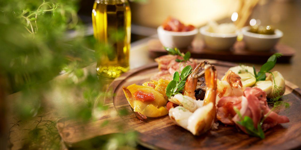 Verschiedene, auf einem Holzbrettchen angerichtetem Speisen - im Vordergrund sind Gewürze zu sehen, im Hintergrund eine Ölflasche und drei kleine Schälchen