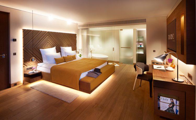 Ein gemütliches Bett mit eleganter Beleuchtung und eine freistehende Badewanne im Schlafzimmer der Kategorie C des BEYOND Hotels