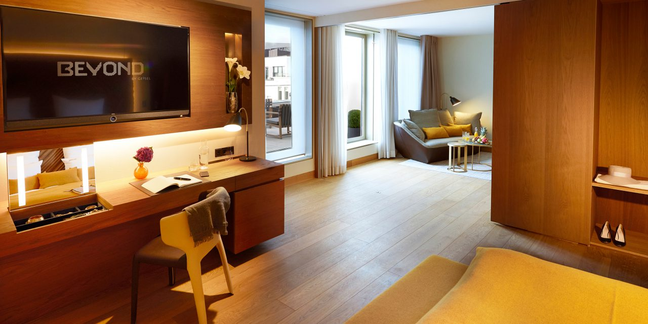 View into a spacious hotel room of the BEYOND-Hotel Munich with a large desk, seating area and panorama windows to a balcony.