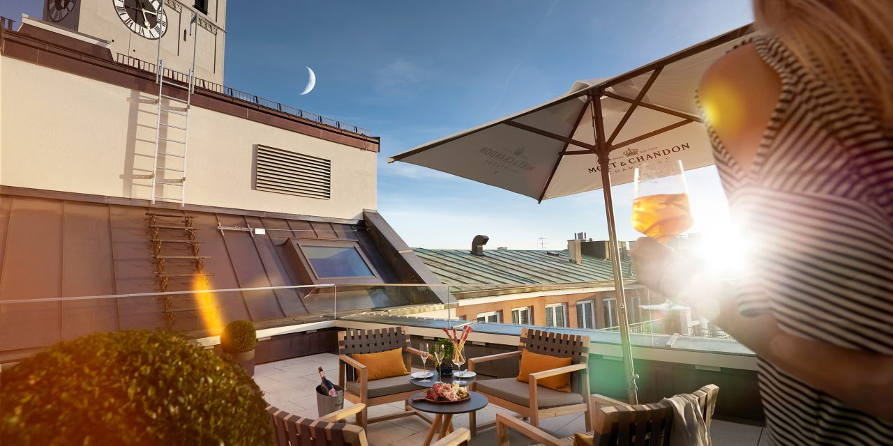 A seating group on the roof terrace of the BEYOND-Hotel Munich with a woman holding a wine glass in her hand on the left side.