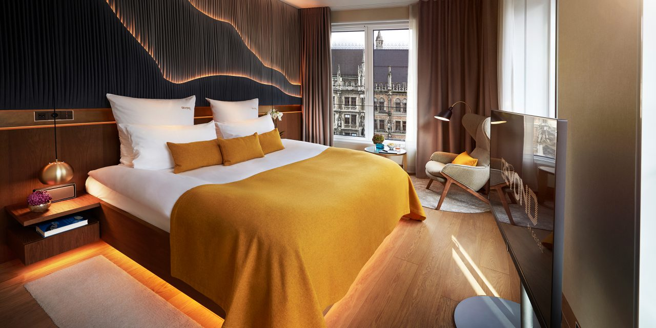 A modernly furnished hotel room with large panorama windows over the Munich Town Hall, a comfortable armchair and a large television set in the BEYOND Hotel.