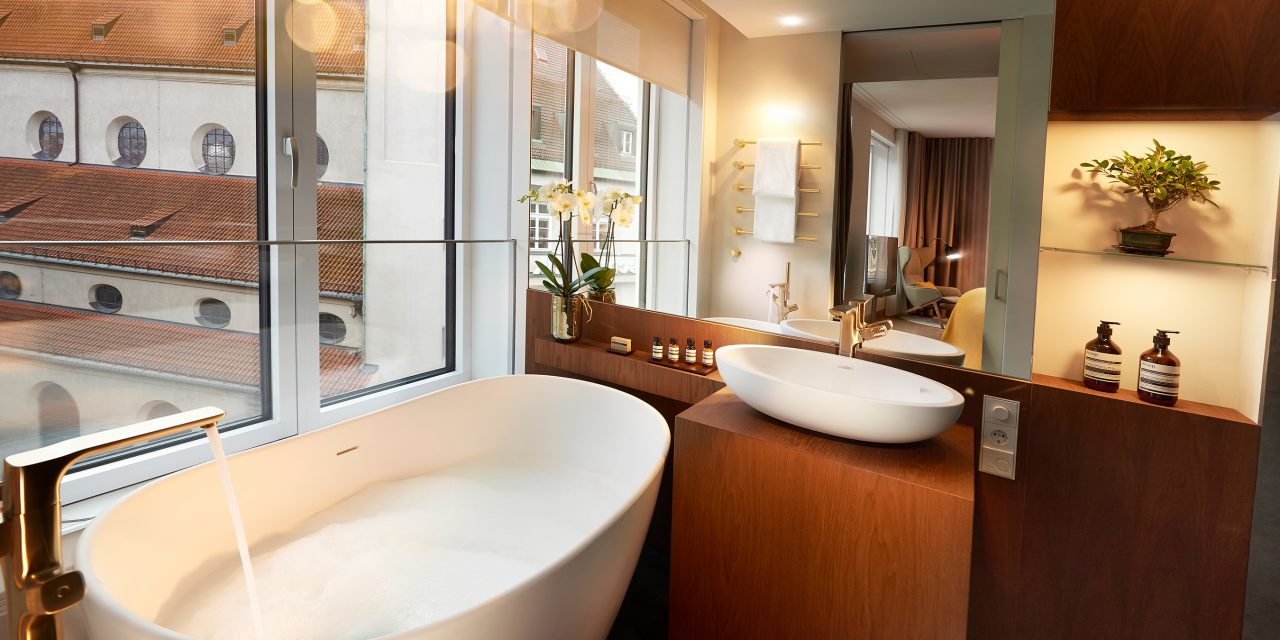 "Modern bathroom with wooden furniture, a free-standing bathtub with a view of the church ""Sankt Peter"""