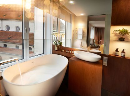 Modern bathroom with wooden furniture, a free-standing bathtub with a view of the church