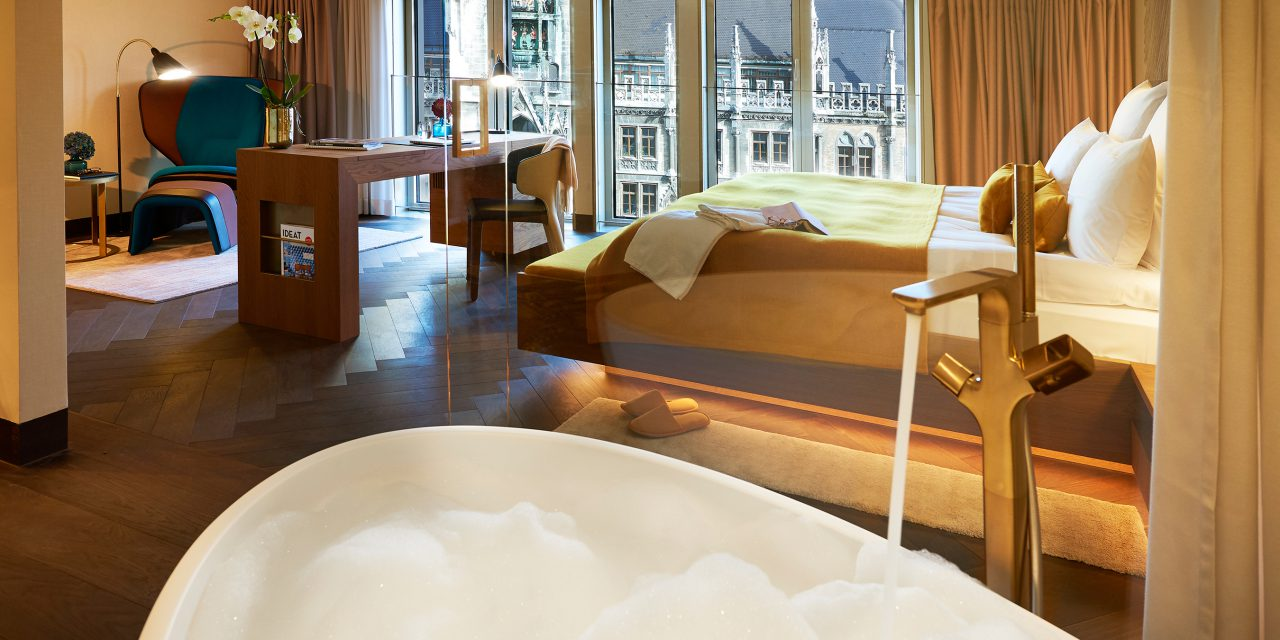 A free-standing bathtub in the BEYOND-Hotel Munich, from which you can look into a light-flooded hotel room with a view of Marienplatz.
