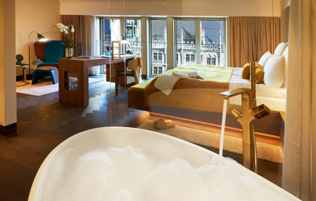 bedroom category M at the BEYOND by Geisel with direct view over the Marienplatz, the hotspot in Munich, Germany, Europe - the bathtub offers a place for foam baths in the heart of Munich