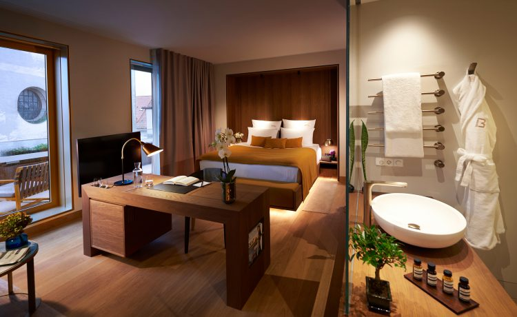 A spacious room in the BEYOND-Hotel Munich with a large desk, a comfortable bed and an open bathroom.