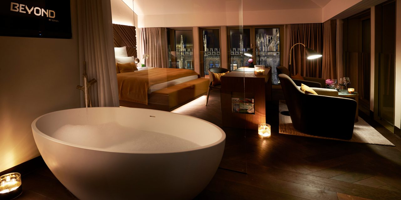 Night mood in a spacious hotel room in the BEYOND-Hotel Munich with a free-standing bathtub